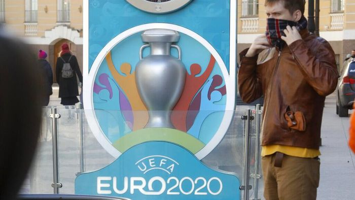 A man covers his mouth with a scarf, standing at a tomb with Euro 2020 emblem in St.Petersburg where UEFA planned to host four UEFA EURO 2020 matches, including a quarter final, in Russia, Tuesday, March 17, 2020. UEFA today announced the postponement of its flagship national team competition, UEFA EURO 2020, due to be played in June and July this year, avoiding placing any unnecessary pressure on national public services involved in staging matches.  For some people the new COVID-19 coronavirus causes only mild or moderate symptoms, but for some it can cause more severe illness.  (AP Photo/Dmitri Lovetsky)