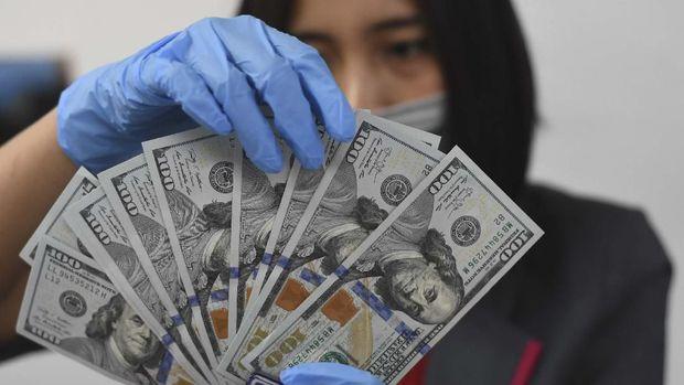 Petugas menata mata uang dolar AS di salah satu gerai penukaran uang asing di Jakarta, Kamis (19/3/2020). Berdasarkan data kurs referensi Bank Indonesia Jakarta Interbank Spot Dollar Rate (JISDOR) hingga pukul 18.00 WIB nilai tukar rupiah terhadap dollar AS melemah ke posisi Rp 15.712 per dollar AS yang disebabkan sentimen negatif pandemik COVID-19. ANTARA FOTO/Indrianto Eko Suwarso/hp.