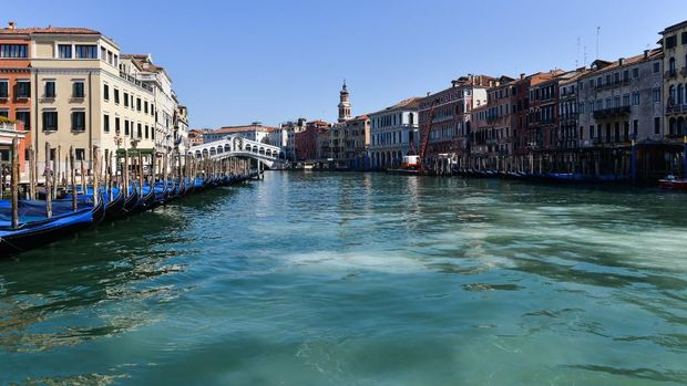 A general view shows clear waters of the Grand Canal near the Rialto Bridge in Venice on March 18, 2020, as a result of the stoppage of motorboat traffic, following the country's lockdown within the new coronavirus crisis. (Photo by ANDREA PATTARO / AFP)