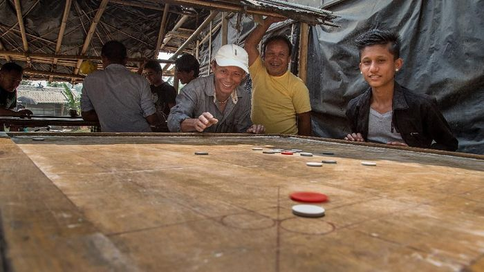 BELDANGI, NEPAL - MARCH 14:  A group of refugees play carrom board during their free time in the Beldangi 2 refugee camp on March 14, 2015 in Beldangi, Nepal. Carrom board is the most played game by refugees in the camps. More than 22,000 Bhutanese refugees still reside in the refugee camps set up in Nepal in the 1990s, after hundreds of thousands of Bhutanese fled the country following a campaign of ethnic cleansing by the Bhutanese Government against the countrys ethnic Nepali population. After more than 20 years in Nepal, over 90% of the refugees have been successfully resettled in third countries, thanks to programs by UNHCR and IOM. Those remaining the camps are supported by several organizations that undertake a wide variety of projects. Helped by remittances sent back to Nepal by families already resettled in other countries, the refugees still in the camps have set up their own small businesses in the camps and the roads near them, roads which are also replete with Nepali-owned businesses who benefit directly from the refugees that are still waiting in Nepal to be resettled in third countries. (Photo by Omar Havana/Getty Images)