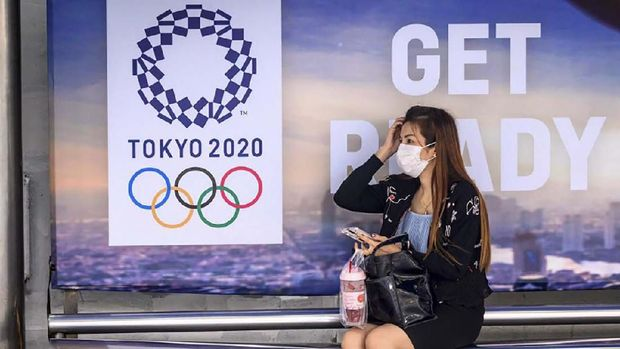 A woman wearing a facemask, amid concerns over the spread of the COVID-19 coronavirus, sits at a bus stop in front of a Tokyo 2020 Olympics advertisement in Bangkok on March 16, 2020. (Photo by Mladen ANTONOV / AFP)
