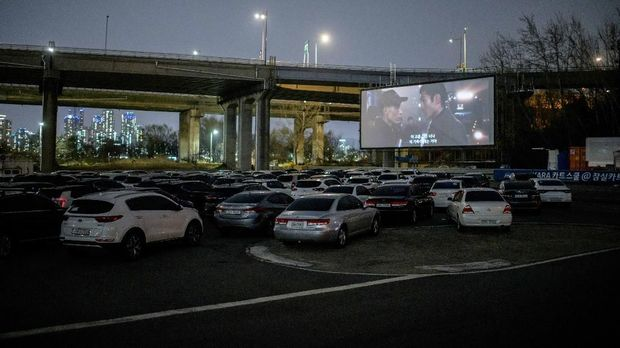In a photo taken on March 21, 2020 an outdoor screen shows a movie at a drive-through cinema in Seoul. - Box office numbers in South Korea -- which has 8,897 confirmed virus cases -- have plummeted in recent weeks due to the epidemic, with authorities urging the public to avoid large crowds. But at drive-in cinemas, moviegoers can enjoy a movie from the comfort of their cars, parked in front of a large outdoor screen. (Photo by Ed JONES / AFP)
