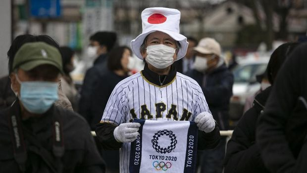 A man wearing a Japanese flag-themed hat shows a towel with a Tokyo 2020 Olympics logo printed on while waiting in line to view the Olympic Flame in Fukushima City, Japan, Tuesday, March 24, 2020. (AP Photo/Jae C. Hong)