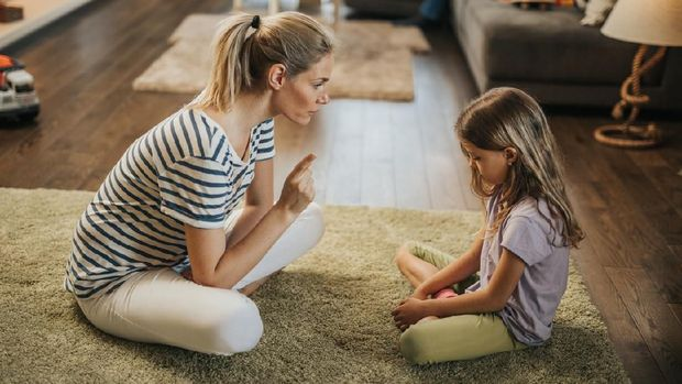 Angry offended little girl ignoring not listening mother words, advice, mum hugging, talking with stubborn, upset daughter at living room, bad upbringing, difficult behavior of child