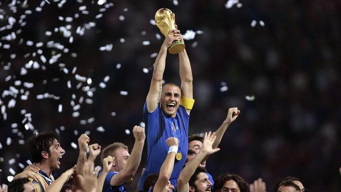 Italian defender Fabio Cannavaro (C) celebrates with the trophy after the World Cup 2006 final football game Italy vs.France, 09 July 2006 at Berlin stadium. Italy won the 2006 football World Cup by defeating France on penalties. AFP PHOTO PASCAL PAVANI (Photo by PASCAL PAVANI / AFP)
