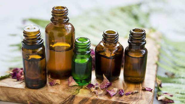 Aromatherapy oil bottles with flowers and green leaves, botanical natural alternative beauty, herbal wellness and spa setting