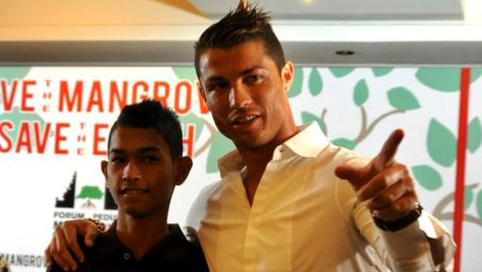 Football player Christiano Ronaldo (R) is reunited with 16-year-old Martunis (L), an Indonesian survivor of the deadly 2004 Aceh tsunami who the Real Madrid star met in 2005 during a mission to assist tsunami victims and gave his family financial assistance. Ronaldo participated in a conservation movement in Indonesia aiming to raise public awareness of the importance of mangrove forests.  AFP PHOTO/SONNY TUMBELAKA (Photo by SONNY TUMBELAKA / AFP)