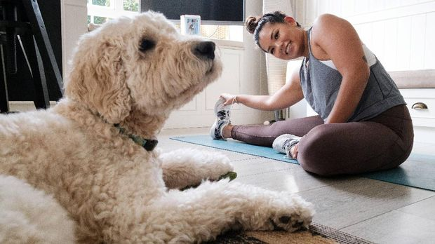 In this picture taken on March 26, 2020, Alison Yuen, 32, who is a Singapore national, takes a fitness class which was recorded by her personal trainer Kristen Handford, 33, as her dog sits nearby in her kitchen in Discovery Bay, on the outlying Lantau Island in Hong Kong. - More than 3.4 billion people have been called on or forced by authorities to stay at home, around 44 percent of the world population, according to a count based on an AFP database. Many are wondering how they can stay healthy during the weeks -- and possibly months -- of self-isolation that lie ahead. Hong Kongers, who live in some of the world's smallest apartments, say it can be done. (Photo by Anthony WALLACE / AFP) / TO GO WITH HongKong-health-virus-fitness,FOCUS by Jerome TAYLOR