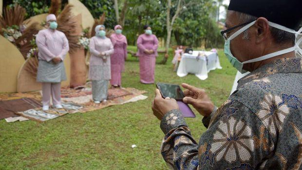 Tamu mengenakan masker saat menghadiri akad nikah pasangan suami-isteri Bayu Amde Winata dan Mike Agnesia yang berlangsung saat tanggap darurat COVID-19 di Kota Pekanbaru, Riau, Sabtu (4/4/2020). Pemerintah Indonesia mengimbau warga yang menikah untuk tidak mengumpulkan orang banyak, menyediakan masker dan pembersih tangan dan lokasinya di tempat terbuka serta menjaga pembatasan jarak fisik, agar tidak mempercepat penyebaran virus Corona. ANTARA FOTO/FB Anggoro/wsj.