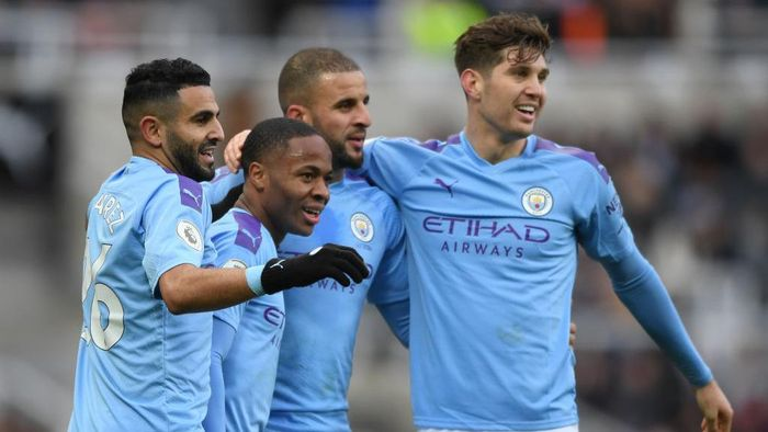 NEWCASTLE UPON TYNE, ENGLAND - NOVEMBER 30: Raheem Sterling of Manchester City celebrates with teammates Riyad Mahrez, Kyle Walker and John Stones after scoring his teams first goal during the Premier League match between Newcastle United and Manchester City at St. James Park on November 30, 2019 in Newcastle upon Tyne, United Kingdom. (Photo by Stu Forster/Getty Images)