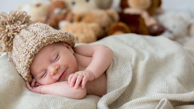 Little newborn baby boy, sleeping in basket, holding toy, posed picture