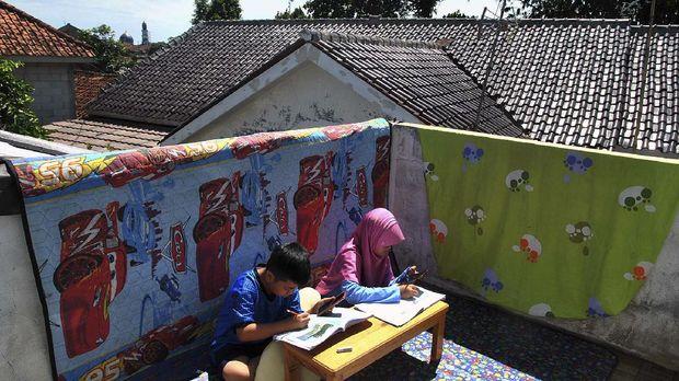 Siswa SD mengerjakan tugas sekolah menggunakan aplikasi daring dari gawai sambil berjemur sinar matahari pagi di rumahnya di Laladon Gede, Desa Laladon, Ciomas, Kabupaten Bogor, Jawa Barat, Selasa (31/3/2020). Gubernur Jawa Barat Ridwan Kamil memperpanjang masa belajar di rumah bagi siswa sekolah SD, SMP, SMA dan SMK atau setara di wilayah Jawa Barat selama dua minggu sampai dengan 14 April 2020 dalam rangka pencegahan penyebaran virus Corona (COVID-19). ANTARA FOTO/Arif Firmansyah/wsj.