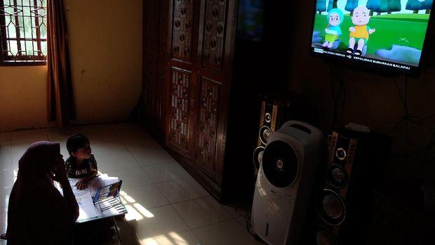 Seorang anak didampingi ibunya belajar dengan melihat tayangan siaran TVRI di rumah mereka, di Deli Serdang, Sumatera Utara, Senin (13/4/2020). Kementerian Pendidikan dan Kebudayaan bekerja sama dengan lembaga penyiaran publik TVRI sejak Senin (13/4) hingga tiga bulan ke depan menyiarkan program belajar bagi siswa mulai dari tingkat pendidikan anak usia dini (PAUD) hingga SMA guna membantu para siswa belajar di rumah selama wabah COVID-19. ANTARA FOTO/Irsan Mulyadi/hp.