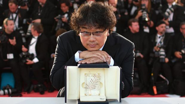 South Korean director Bong Joon-Ho poses during a photocall with his trophy after he won the Palme d'Or for the film