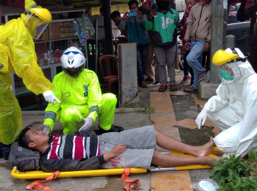 Pria Pingsan di Jalan, Polisi Evakuasi Pakai Jas Hujan