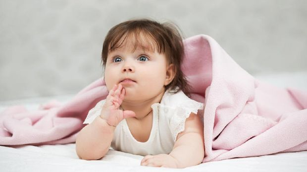 Portrait of baby girl lying on blanket indoors