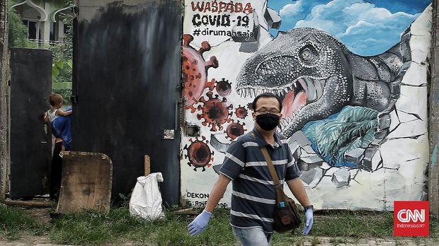 Warga melintasi lukisan 3D yang menggambarkan sebaran virus Corona (Covid 19) yang semakin ganas di tembok dekat dengan Stasiun Depok Baru. Jumat (17/4/2020). CNN Indonesia/Andry Novelino