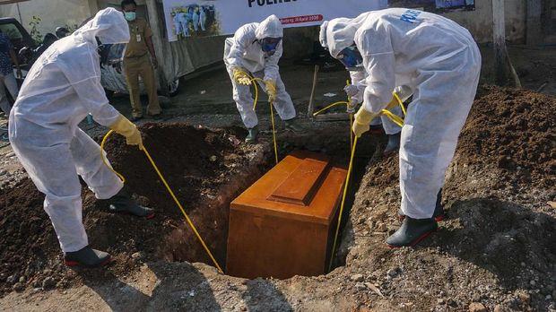 Petugas kepolisian melakukan simulasi pemakaman jenazah pasien positif positif COVID-19 di Mapolres Batang, Jawa Tengah, Senin (20/4/2020). Polres Batang bekerja sama dengan pihak rumah sakit daerah melakukan pelatihan pemakaman jenazah COVID-19 kepada anggota polisi yang menjadi petugas cadangan pemakaman dengan menggunakan alat pelindung diri (APD) yang lengkap sesuai prosedur. ANTARA FOTO/Harviyan Perdana Putra/wsj.