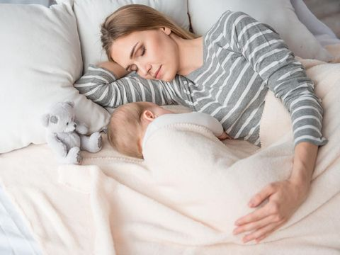 Beautiful mom lying at the back of the baby while the infant is sleeping on the white bed. Asian mother looking at the baby which is her child with love and care.