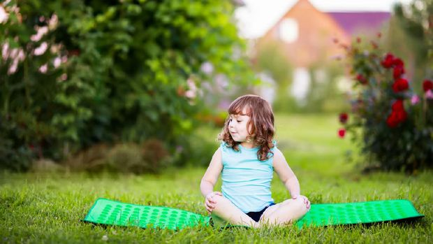 Kid doing fitness exercises outdoors at summer day. Yoga for kids, active healthy life. Fitness. Sport for little children.