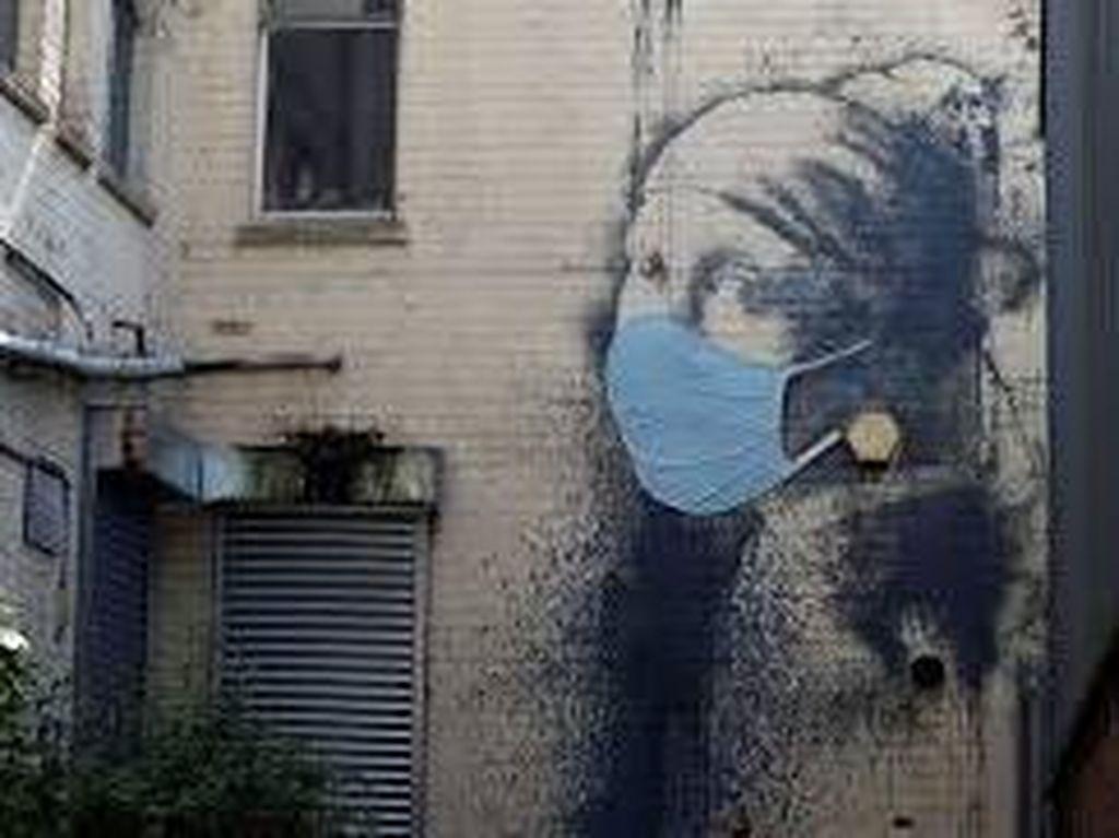 Pandemi Belum Mereda, Banksy Buat Mural Perempuan Bermasker