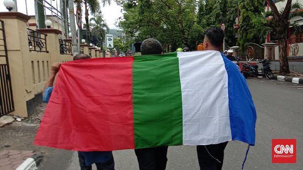 Tiga orang kelompok Front Kedaulatan Maluku (FKM) yang berafiliasi dengan Republik Maluku Selatan (RMS) membawa bendera Benang Raja di Polda Maluku, Sabtu (25/4).