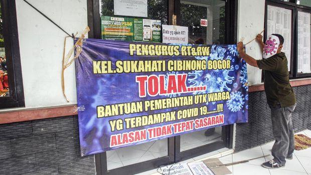 Warga beserta pengurus RT dan RW membawa poster tuntutan serta menggunakan toppeng saat melakukan aksi unjuk rasa di Kantor Kelurahan Sukahati, Cibinong, Bogor, Jawa Barat, Senin (27/4/2020). Aksi tersebut menuntut adanya ketidak sinkronan data penerima bantuan sosial warga terdampak COVID-19, serta bantuan tersebut dinilai tidak tepat sasaran. ANTARA FOTO/Yulius Satria Wijaya/hp..