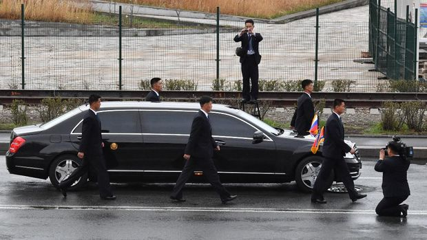 Bodyguards surround the car of North Korean leader Kim Jong Un as it drives away after a wreath-laying ceremony at a WWII memorial in the far-eastern Russian port of Vladivostok on April 26, 2019. (Photo by Yuri KADOBNOV / AFP)