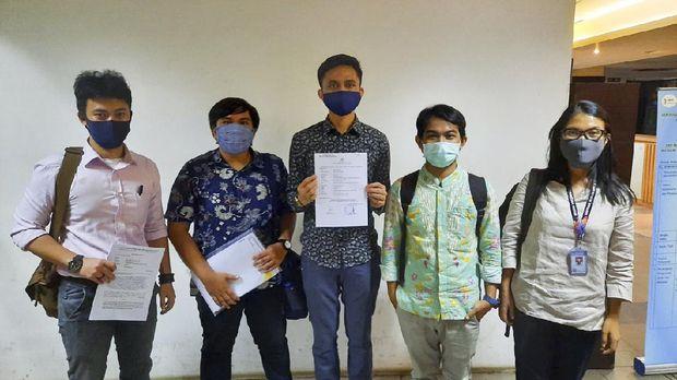 Peneliti kebijakan publik dan pegiat demokrasi, Ravio Patra (tengah) melaporkan dugaan peretasan akun WhatsApp miliknya ke Polda Metro Jaya, Senin (27/4).