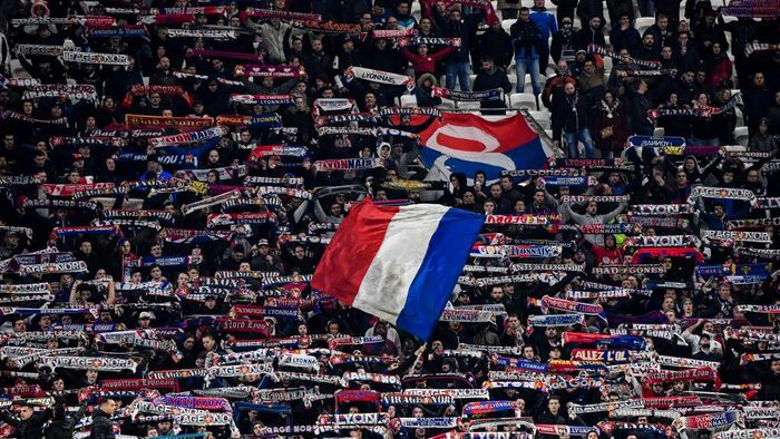 Lyons supporters wave flags and hold banners during the French Cup semi-final football match between Olympique Lyonnais (OL) and Paris Saint-Germain (PSG) at the Groupama Stadium in Decines-Charpieu, centraleastern France, on March 4, 2020. (Photo by Philippe DESMAZES / AFP)