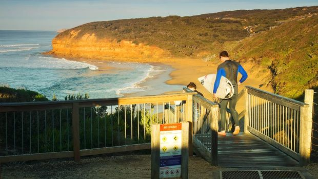 Bells Beach, Australia - May 13, 2014: Surfers head down a staircase leading to Bells Beach at sunrise. A renowned surf beach, the Rip Curl Pro is held here every Easter.