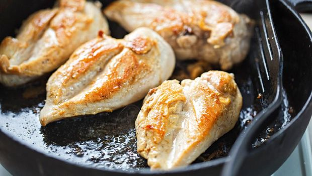 Fried chicken breasts on vegetable oil, iron cast pan