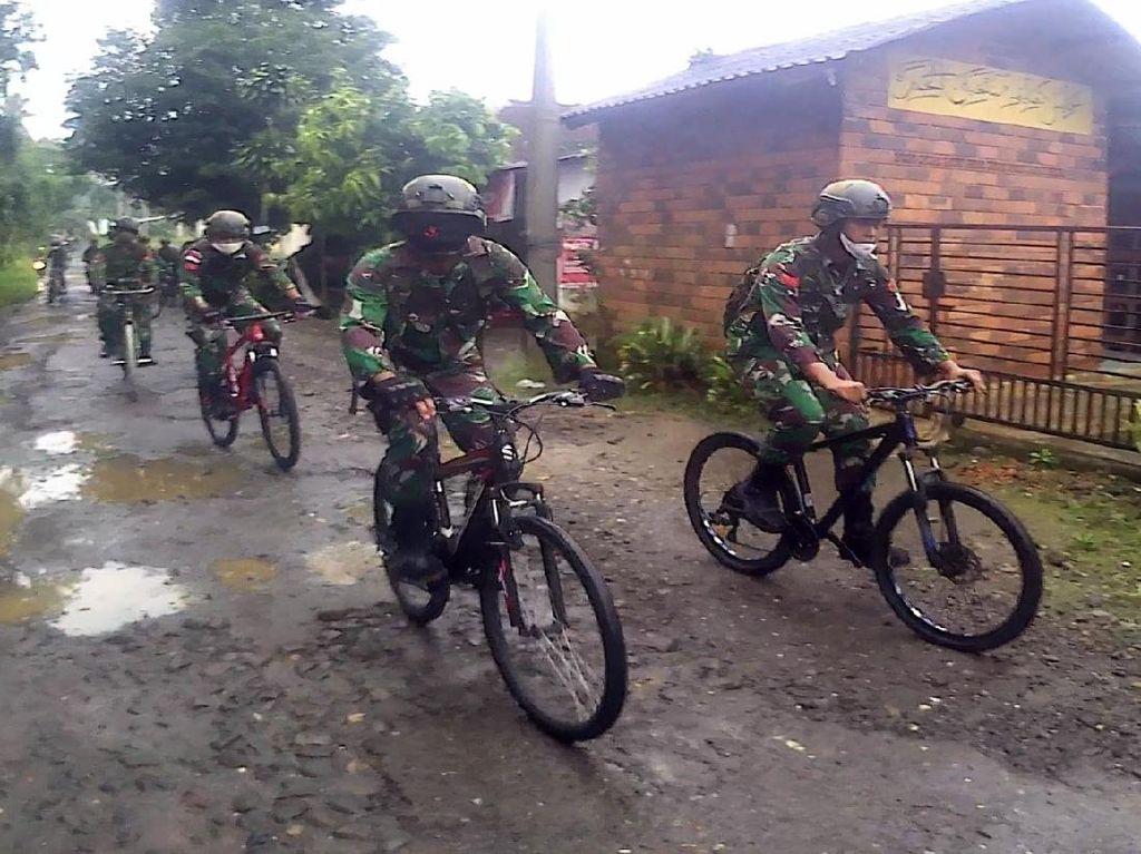 Anggota TNI Bagikan Paket Sembako ke Warga Pakai Sepeda & Trail