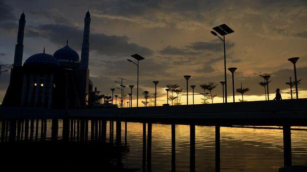 Suasana Masjid Terapung Amirul Mukminin di Anjungan Pantai Losari yang telah ditutup untuk umum saat matahari tenggelam di Makassar, Sulawesi Selatan, Jumat (17/4/2020). Pembatasan Sosial Berskala Besar (PSBB) dalam percepatan penanganan COVID-19 di Kota Makassar akan diterapkan pada Jumat (24/4/2020) mendatang. ANTARA FOTO/Abriawan Abhe/wsj.