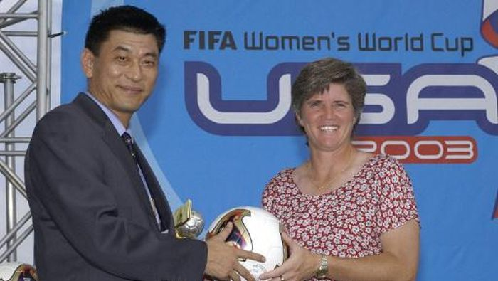 Ma Liangxiang (L), the head coach of the Chinese Womens National Soccer team, passes the ball to U.S. Womens National Soccer Team head coach April Heinrichs in a ritual to the host country prior to the FIFA Womens World Cup USA 2003 Draw 17 July, 2003 at the Home Depot Center in Carson, California. The 16 qualified teams were divided into four groups of four teams each. AFP PHOTO/VINCE BUCCI (Photo by VINCE BUCCI / AFP)