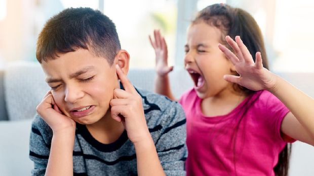 Shot of a little girl screaming in her big brother's ears while playing in the living room at home
