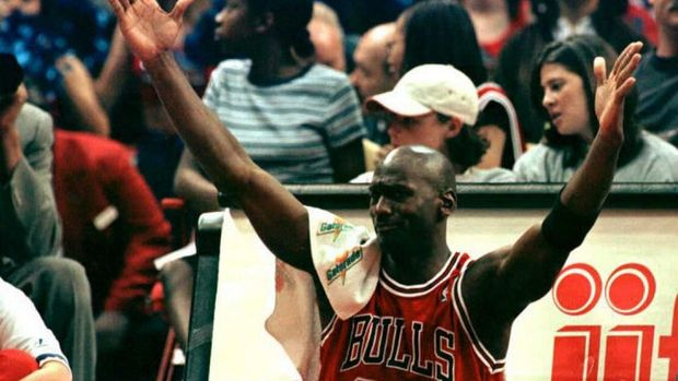While sitting by the scorers table before returning to play, Michael Jordan of the Chicago Bulls celebrates after a teammate scored a three point shot in the fourth quarter of Chicago's 103-93 win over the Washington Bullets at USAir Arena in Landover, Maryland 21 April. The Bulls ended the regular season with a record of 72-10. AFP PHOTO/Ted MATHIAS (Photo by TED MATHIAS / AFP)