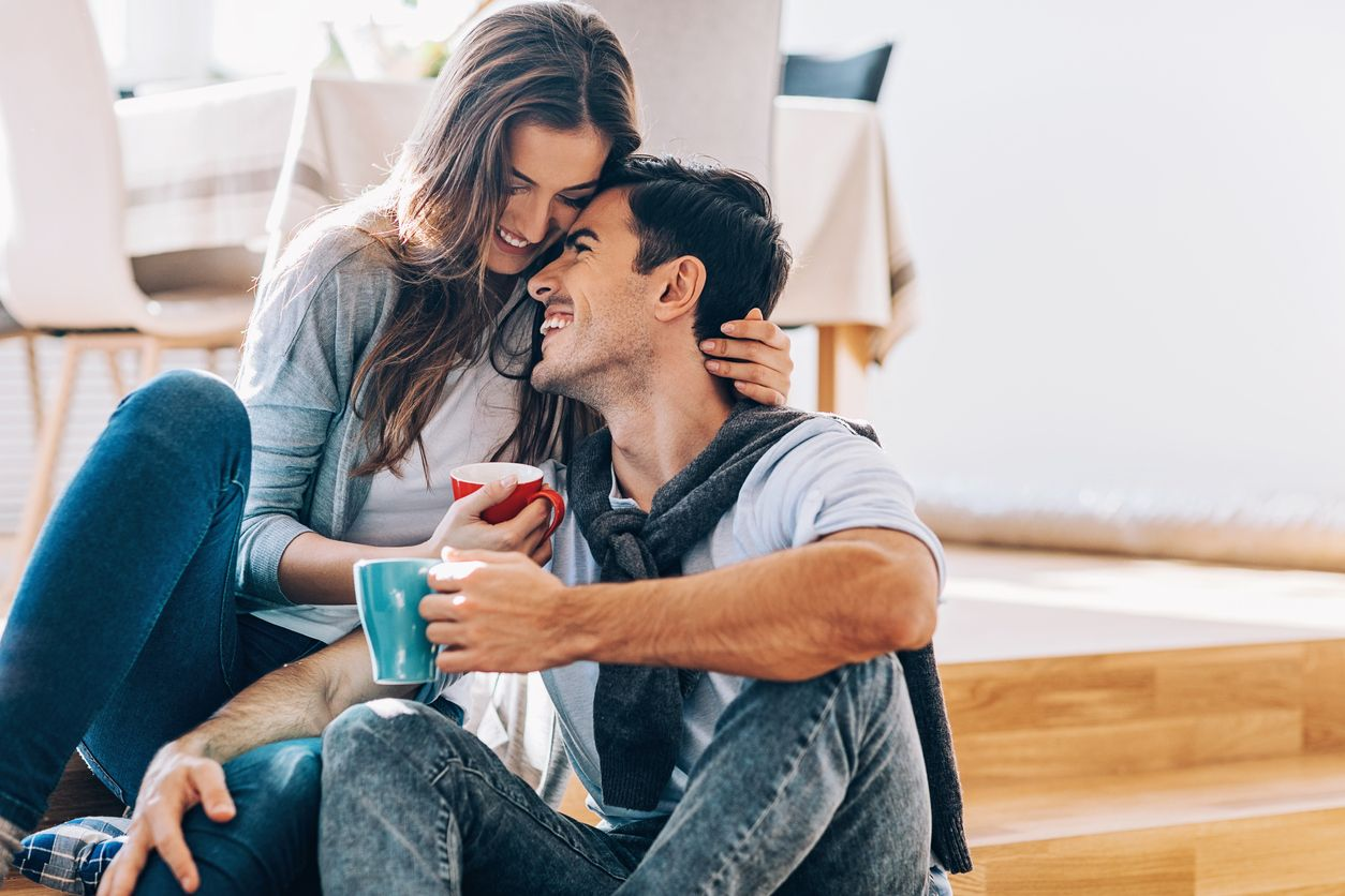 Happy couple in love sitting on the floor, embracing, smiling and drinking coffee, with copy space.