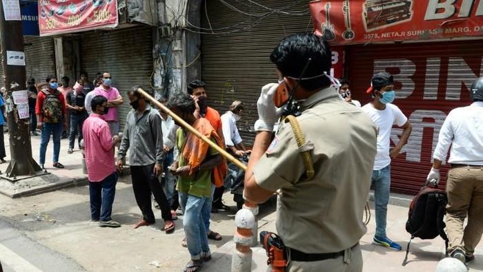 Polisi memukuli warga yang berdesakan saat beli miras (AFP)