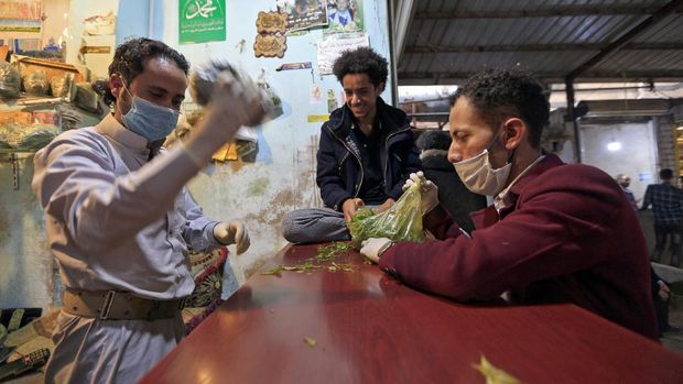 A Yemeni man buys qat, the ubiquitous mild narcotic, at a market in the capital Sanaa on May 1, 2020. - While most of the world's markets have closed to curb the spread of coronavirus, in Yemen's capital Sanaa, downtown districts selling qat -- the ubiquitous mild narcotic -- still bustle with people. Flouting social distancing rules, Yemenis jostle to select bunches of the chewable leaf from vendors packed into the narrow laneways crowded with stalls. (Photo by Mohammed HUWAIS / AFP)
