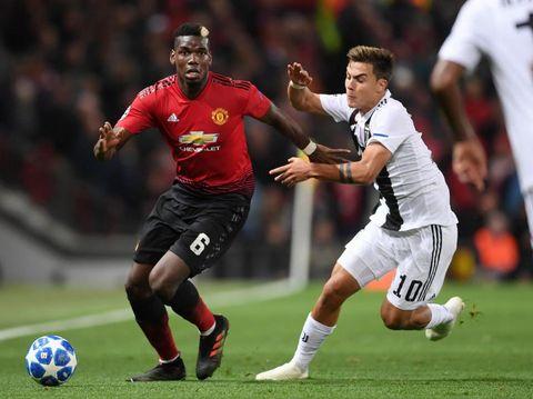Dybala kala hendak merebut bola dari Pogba di laga MU vs Juventus.