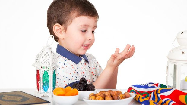 Young Muslim boy praying to Allah while waiting for iftar( breakfast ) in Ramadan
