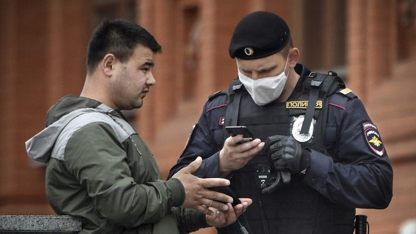 A man shows his digital ID to a police officer in downtown Moscow on May 6, 2020, amid the spread of the new coronavirus COVID-19. (Photo by Alexander NEMENOV / AFP)