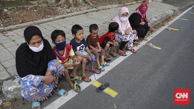 Warga antre mengambil takjil yang disediakan pengurus RT 005 RW 006 kawasan Cempaka Putih Raya,Jakarta, Selasa, 12 Mei 2020. CNNIndonesia/Safir Makki