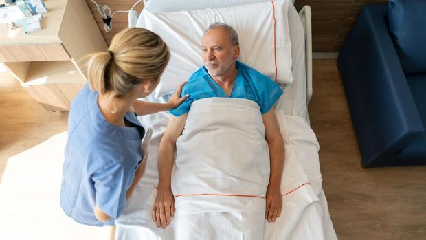 Beautiful nurse comforting senior hospitalized patient lying down on bed talking to him - Healthcare concepts