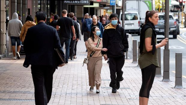People walk on a street in Wellington on May 14, 2020. - New Zealand will phase out its coronavirus lockdown over the next 10 days after successfully containing the virus, although some restrictions will remain, Prime Minister Jacinda Ardern announced on May 11. Ardern said that from May 14 shopping malls, restaurants, cinemas and playgrounds will reopen -- with the country moving to Level Two on its four-tier system. (Photo by Marty MELVILLE / AFP)