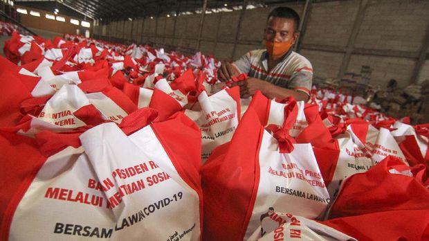 Pekerja menata bantuan paket sembako dan beras dari Presiden Jokowi di Gudang Koperasi Rasra, Cimanggis, Depok, Jawa Barat, Kamis (14/5/2020). Pemerintah pusat mendistribusikan sebanyak 123.881 paket sembako bagi masyarakat Keluarga Penerima Manfaat (KPM) di Kota Depok guna meringankan beban ekonomi di tengah pandemi COVID-19. ANTARA FOTO/Asprilla Dwi Adha/aww.