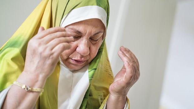 Portrait of an elderly Muslim woman praying