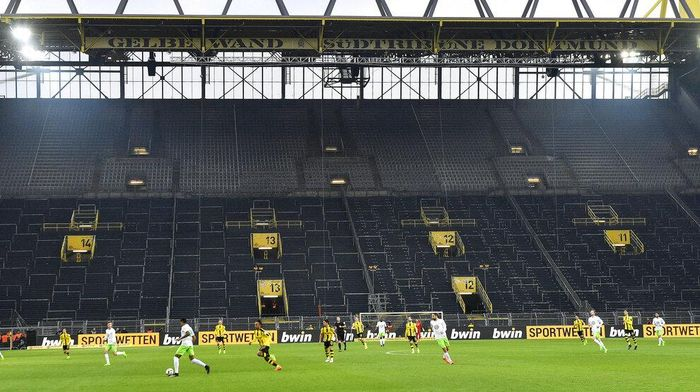 FILE - In this Feb. 18, 2017 file photo, players challenge for the ball in front of the empty south tribune because of a ban following fan trouble during the German Bundesliga soccer match between Borussia Dortmund and VfL Wolfsburg at Germanys biggest stadium in Dortmund, Germany. Bundesliga will now restart on May 16, 2020 when Dortmund will play the derby against Schalke at home without spectators due to the coronavirus outbreak. (AP Photo/Martin Meissner, file)