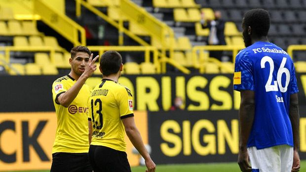 Dortmund's Achraf Hakimi, left, gestures to teammate Raphael Guerreiro after he scored his second goal, theirs side's fourth, during the German Bundesliga soccer match between Borussia Dortmund and Schalke 04 in Dortmund, Germany, Saturday, May 16, 2020. The German Bundesliga becomes the world's first major soccer league to resume after a two-month suspension because of the coronavirus pandemic. (AP Photo/Martin Meissner, Pool)